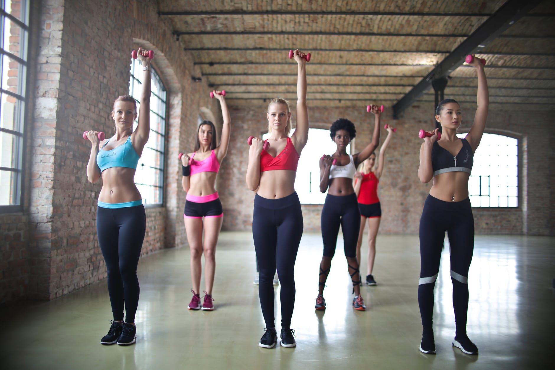 women s assorted sports bras raising their pink dumbbells