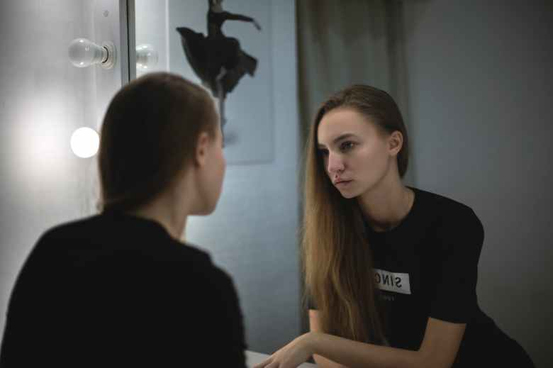 woman in black shirt facing mirror